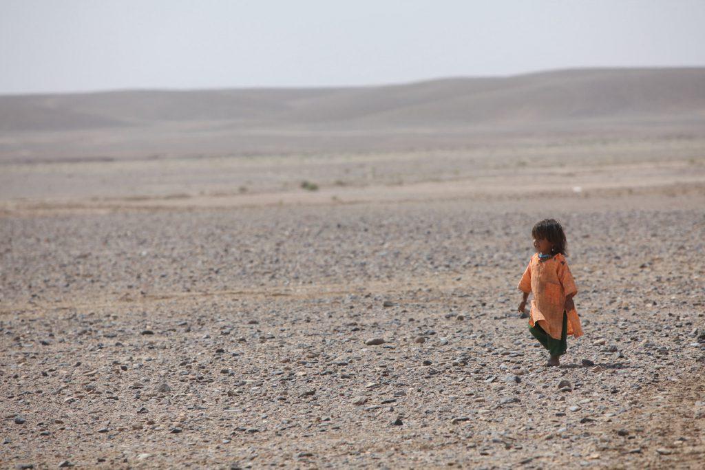 Афганская девочка сидит посреди пустыни