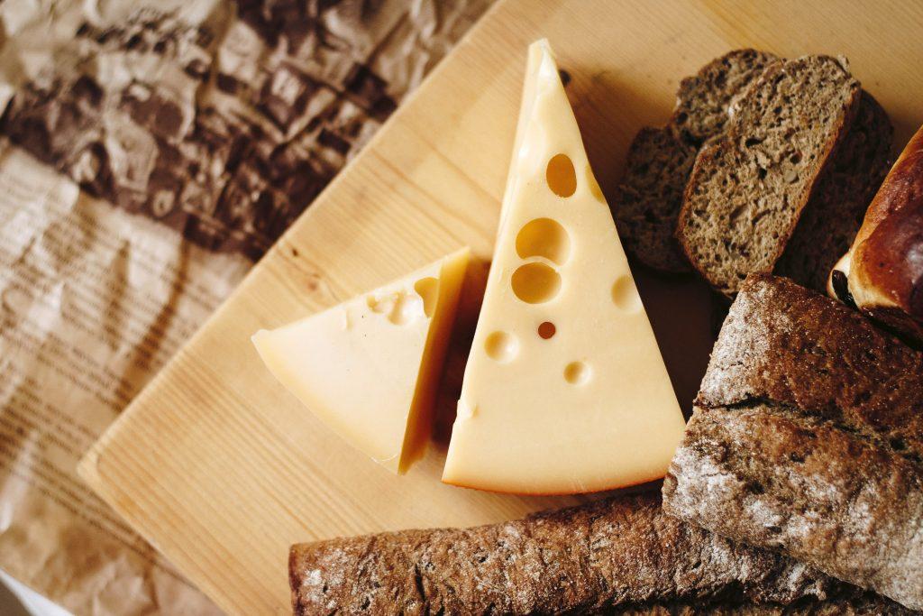 Швейцарский сыр и черный хлеб на деревянной доске