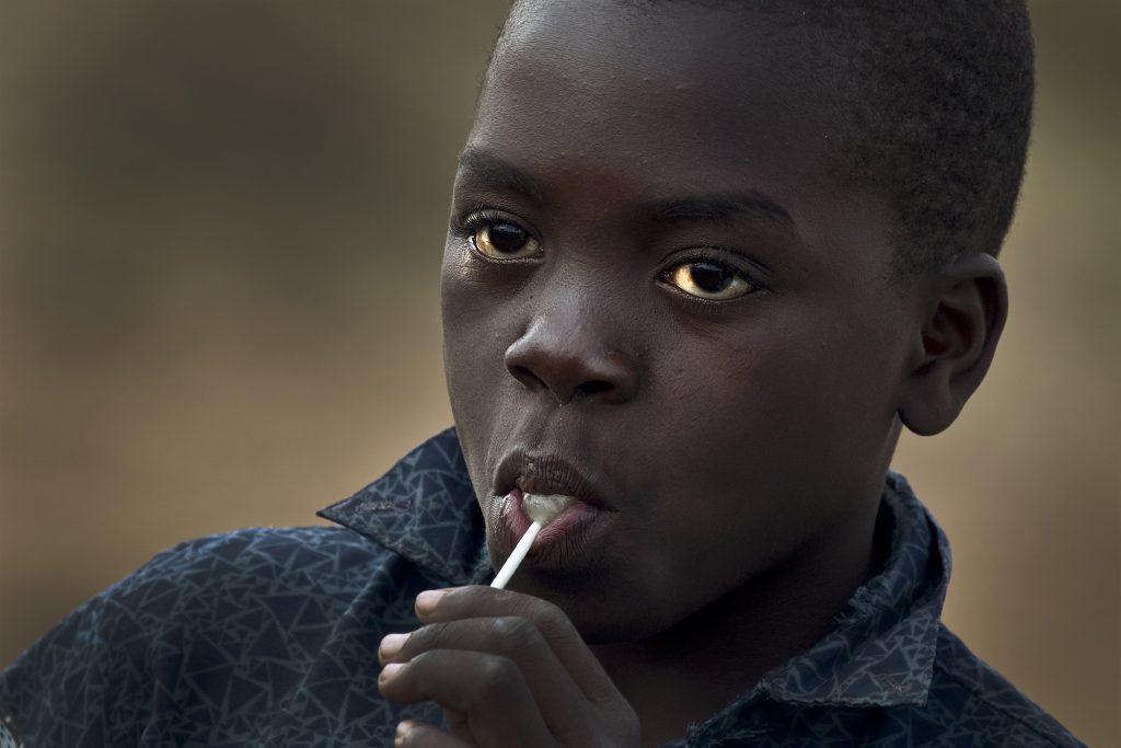 Маленький ребенок сосет конфету