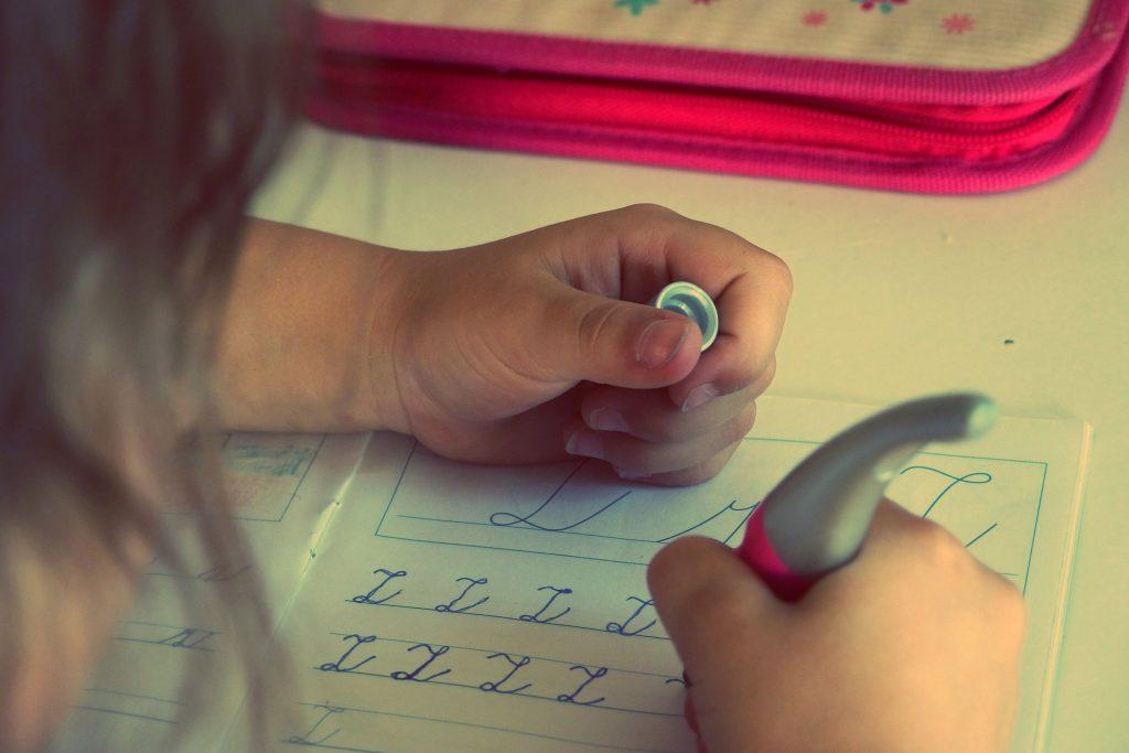 Девочка учится писать в тетради буквы алфавита фото