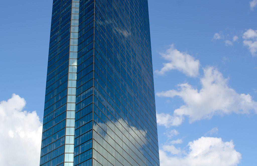 Белые облака отражаются в окнах небоскреба