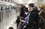 Путешественники стоят в масках в аэропорту фото