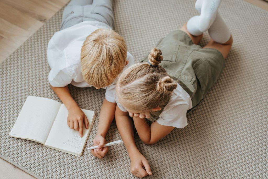 Дети мальчик и девочка делают дома уроки