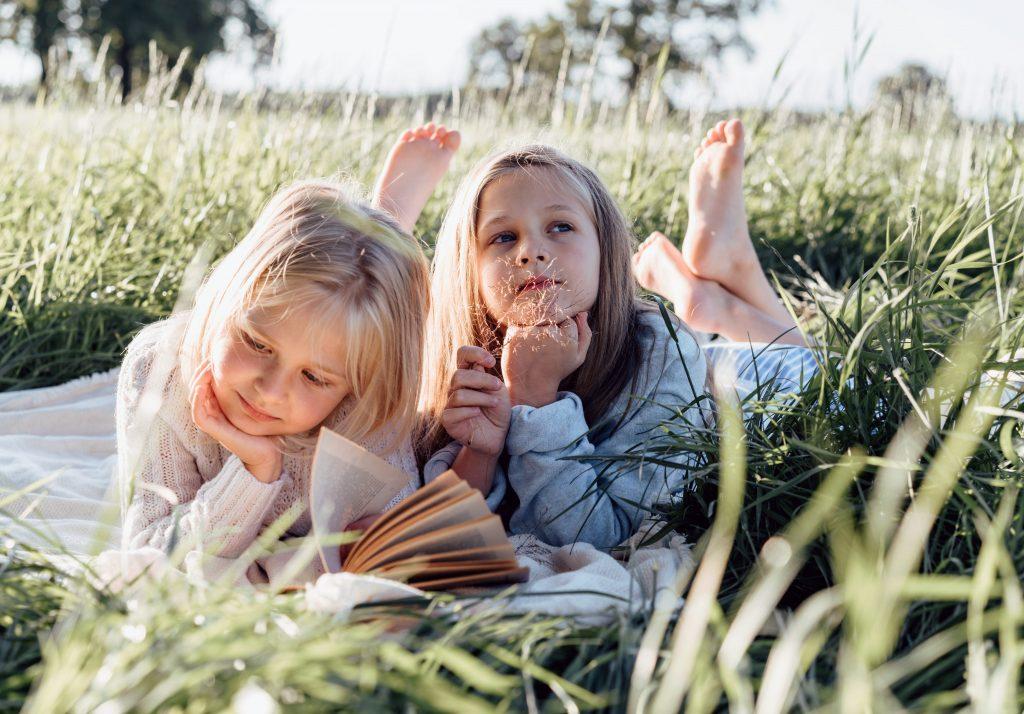 Пикник. Дети девочки читают книгу в поле на подстилке на пикнике