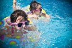 Маленькие девочки плавают в бассейне, учатся плавать