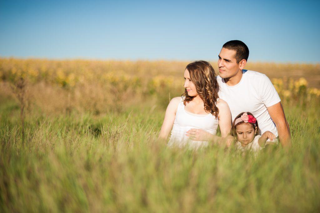 Родители и ребенок сидят в поле среди травы фото