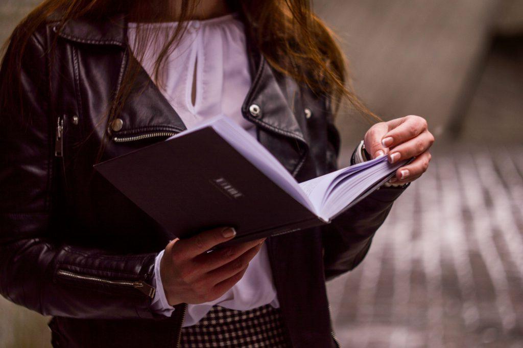 Школьница читает свой блокнот дневник фото