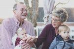 Дедушка и бабушка держат на руках внуков фото