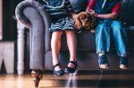 Дети мальчик и девочка сидят на диване с домашней собакой