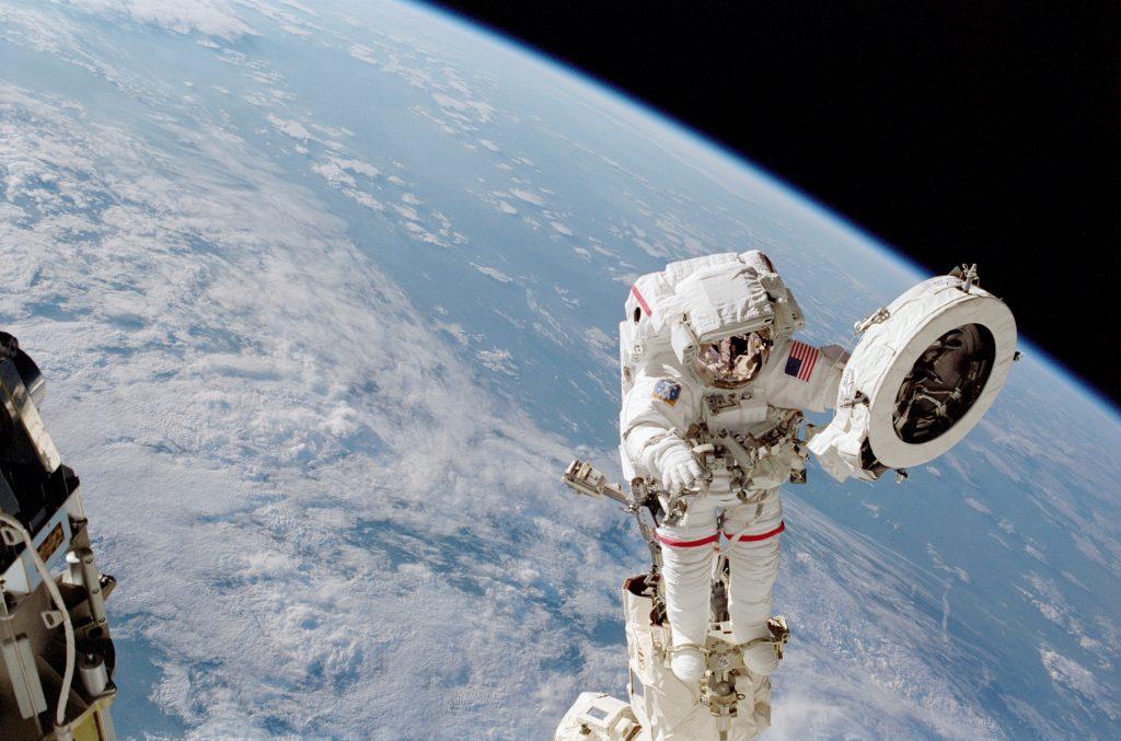 Космонавт работает в космосе на космической станции