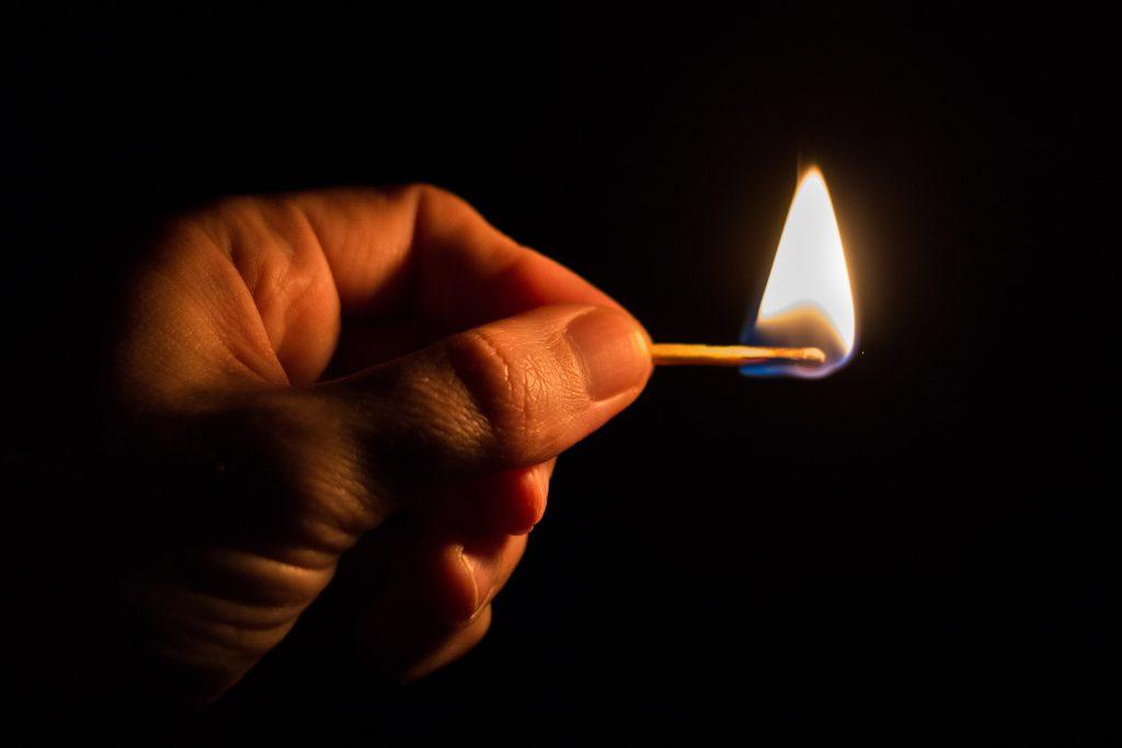 Горящая спичка в руке - пламя и огонь от спички