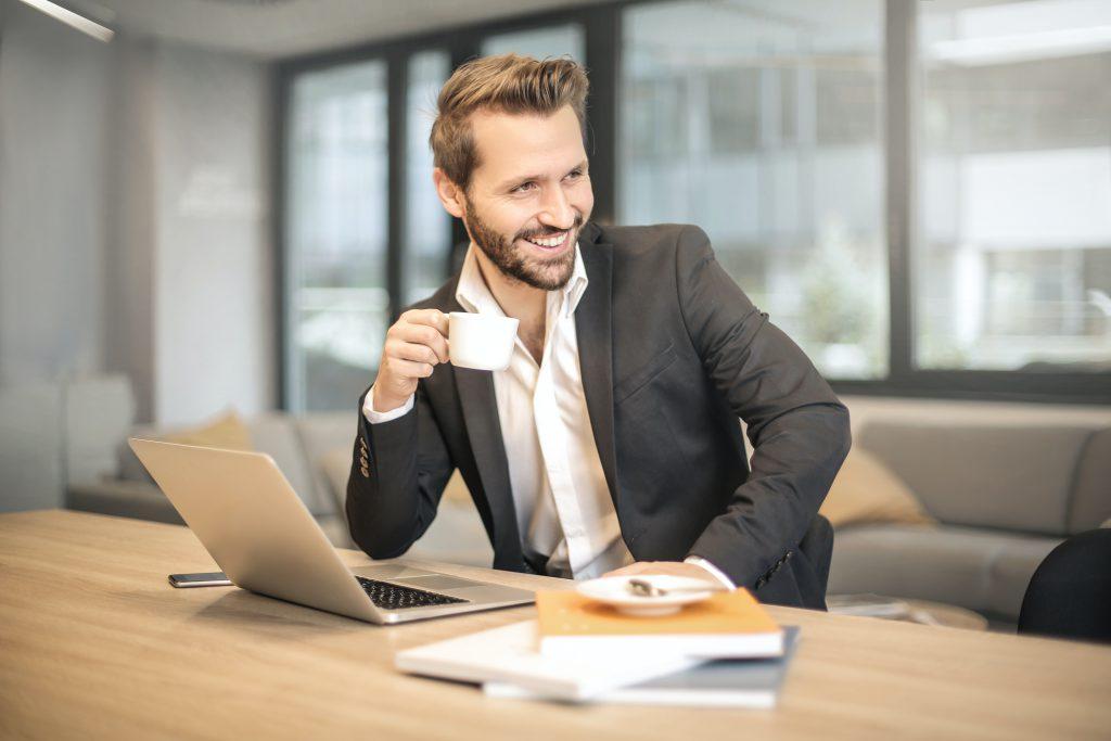 Мужчина в офисе пьет кофе и улыбается фото