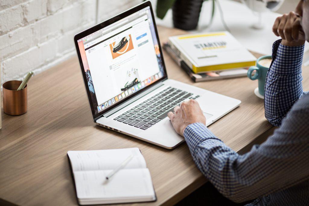 Мужчина сидит за ноутбуком и работает фото