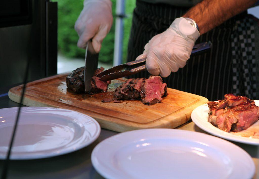 Мужчина повар готовит еду в ресторане - режет мясо
