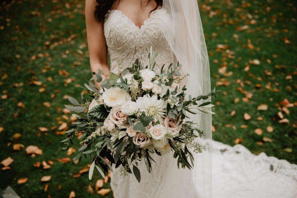 Невеста в белом платье на свадьбе, в руках свадебный букет