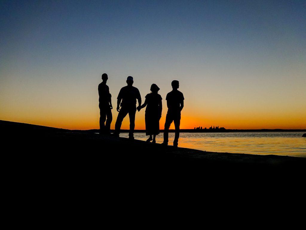 Силуэты семьи на фоне ночного неба на закате
