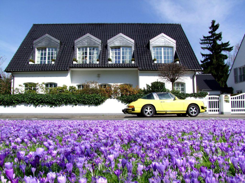 Авто Porsche Carrera (Порше Каррера), цветы крокусы и старый дом в Германии
