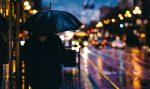 Человек стоит под зонтиком в дождь в городе
