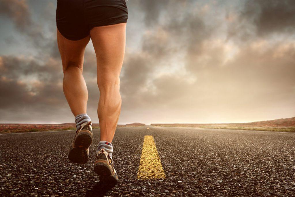 Спортсмен бегун бежит по дороге