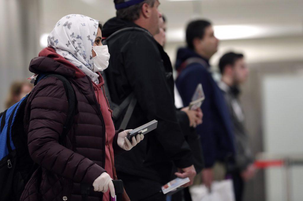 Путешественники в масках в аэропорту фото