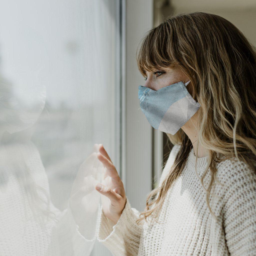 Женщина в маске смотрит в окно фото