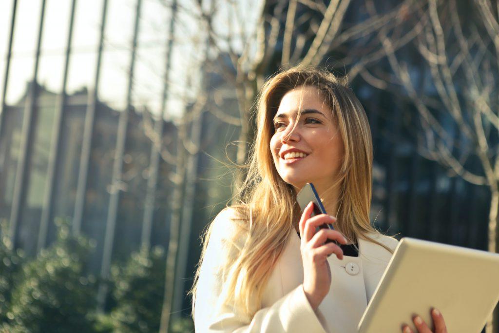 Фото девушки в деловой одежде на улице с телефоном в руке