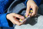 Женщина держит таблетки в руках
