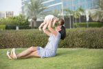 Молодая мать держит ребенка на руках фото